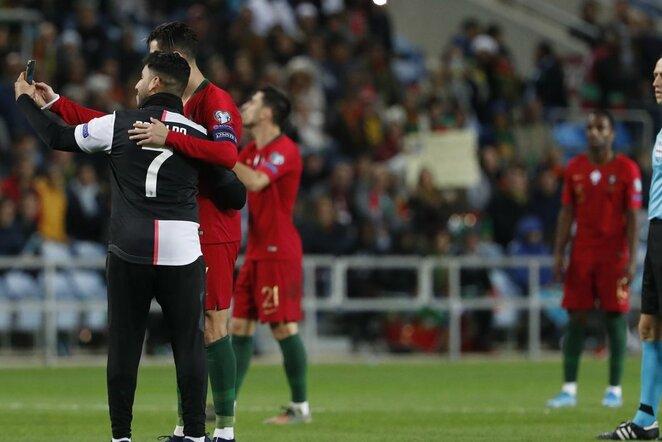 C.Ronaldo pasidarė asmenukę su į aikštę įsiveržusiu fanu   Scanpix nuotr.